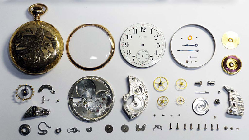 A deconstructed watch with all the gears and parts